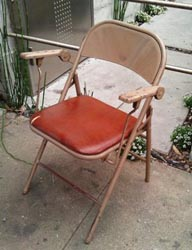 Steel folding chair with arms.